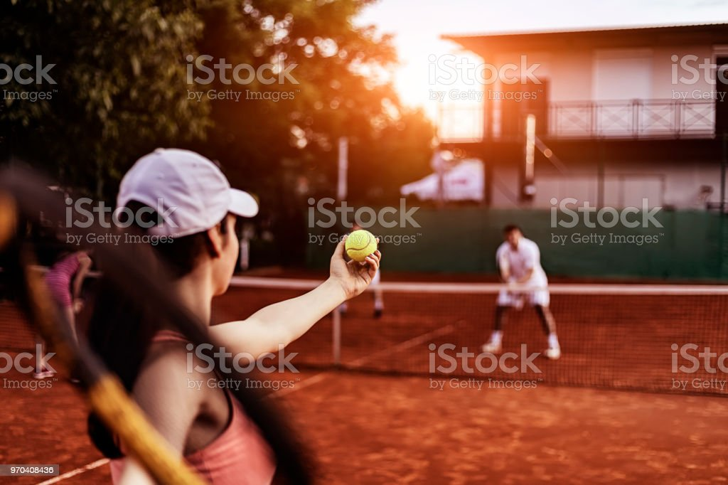 Mixed doubles player playing tennis on the clay tennis court stock photo