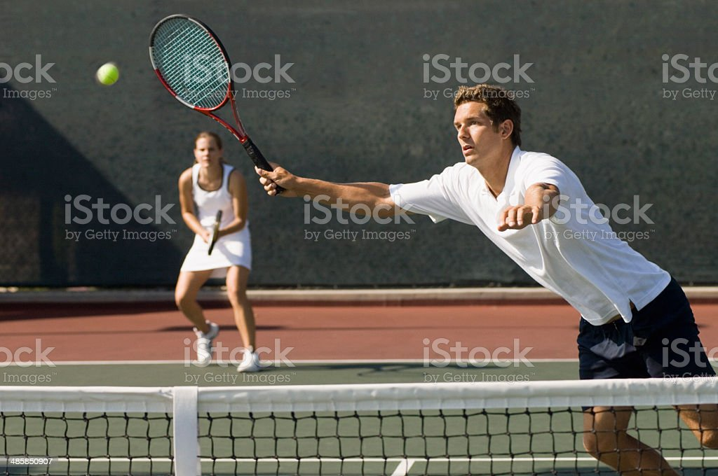Mixed Doubles Player Reaching For Ball stock photo