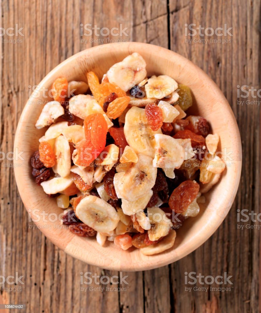Mixed dried fruit in a bowl on a wooden surface stock photo
