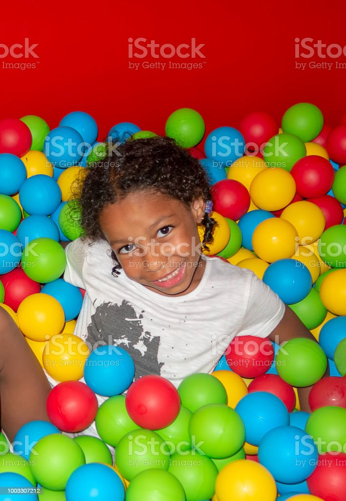 Mixed ethnicity little smiling girl falling among the colorful plastic balls stock photo