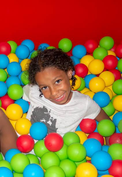 gemischte herkunft wenig lächelndes mädchen fallen unter die bunten plastikbällen - jamaikanische party stock-fotos und bilder