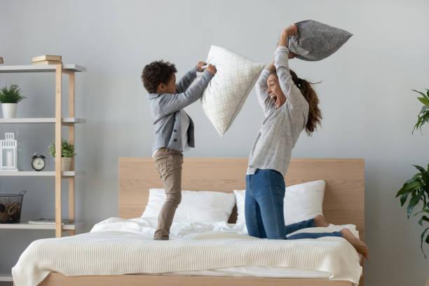 la maman et le fils mélangés d'ethnicité apprécient la lutte d'oreiller sur le lit - matelas photos et images de collection