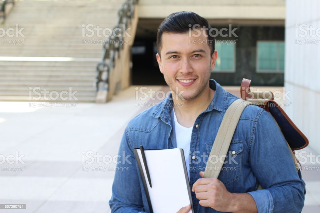 Mixed ethnicity student smiling on campus.