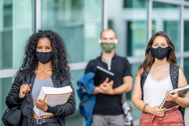 3 mixed ethnicity students wearing masks on campus stock photo