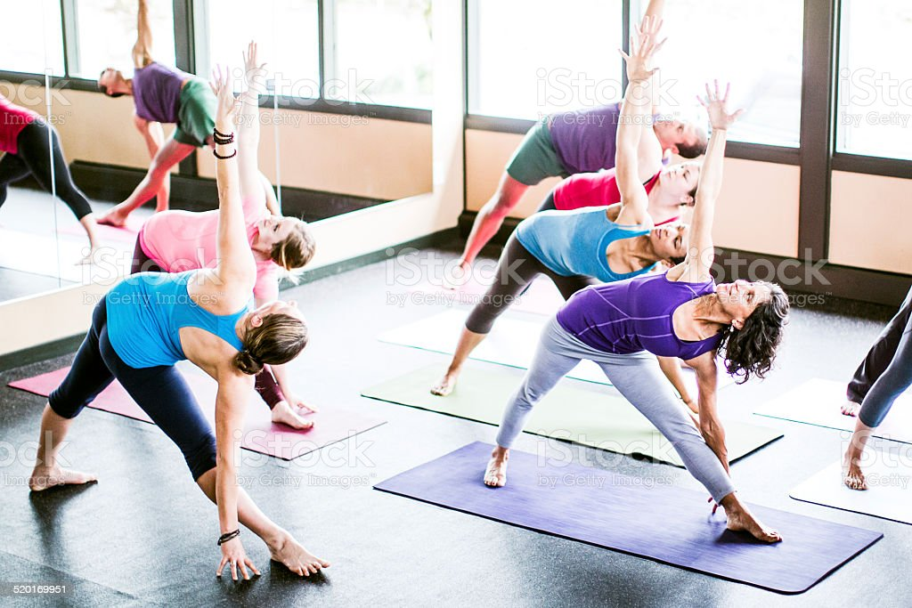 A multi ethnic group of men and woman practice different yoga forms,...