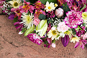 Mixed flower funeral wreath on pink stone.