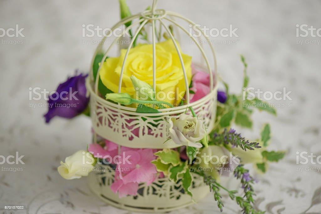 Arreglo de flores mixtas con una rosa amarilla grande en un birdcage decorativo vintage como un centro de mesa boda - foto de stock
