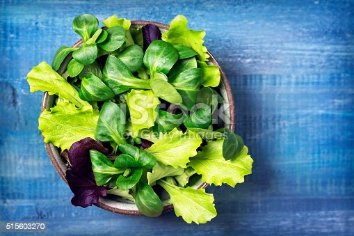 Mixed green salad leaves in a bowl on a blue background