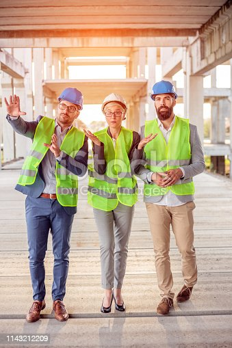 1166176793 istock photo Mixed group of architects walking through prefabricated concrete construction site, inspecting work progress 1143212209