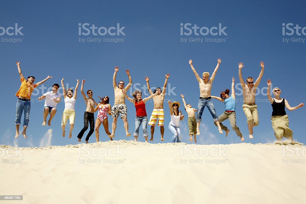 Mixed group of people leaping atop a sand dune with blue sky royalty-free stock photo