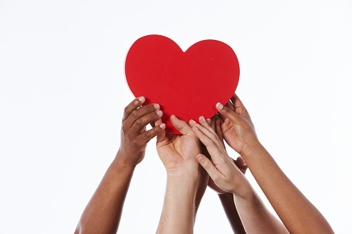 A large group of hands of various ethnic groups reach up to cradle a large red heart together.