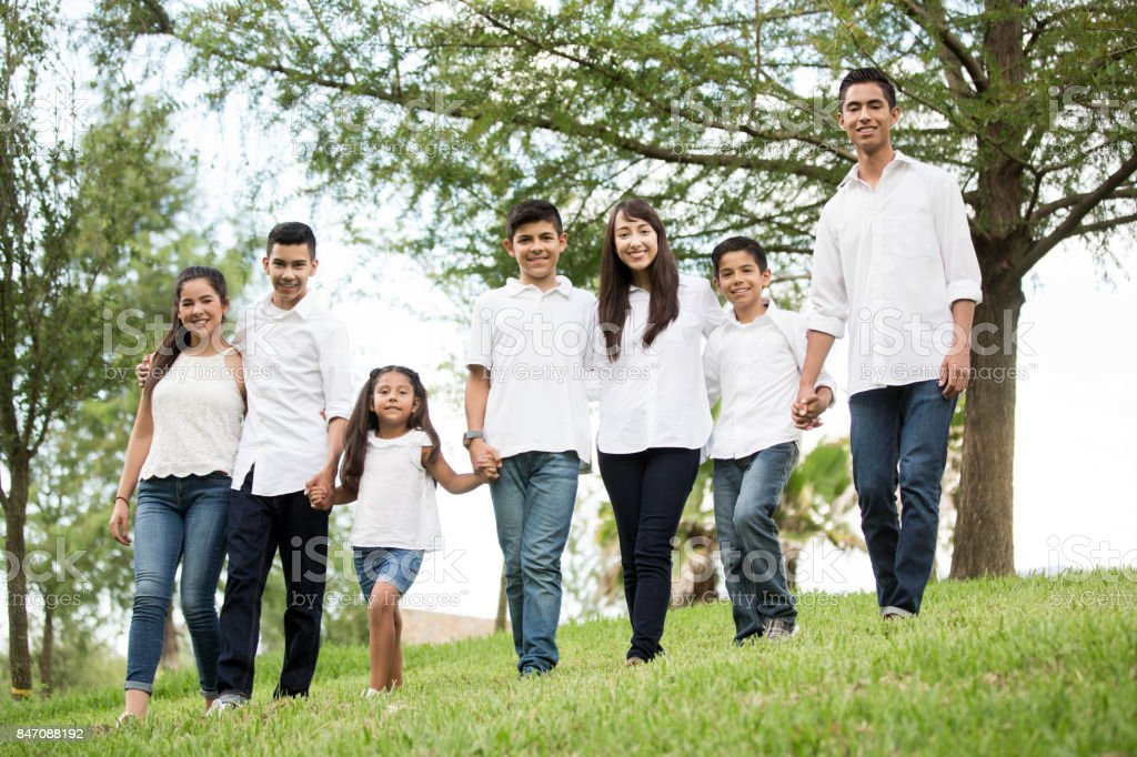 Mixed group of seven children and teenagers standing outdoors stock photo