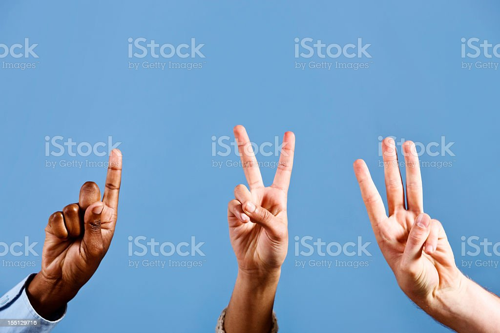 Mixed hands count out 1, 2, 3, against blue background stock photo