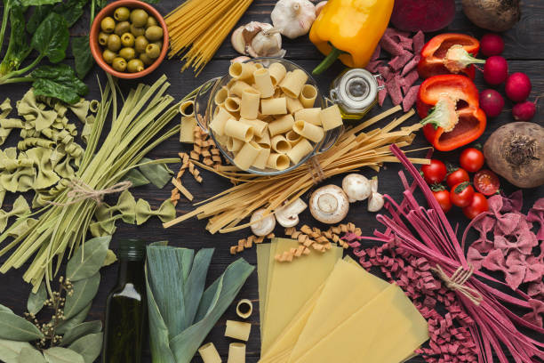 Mixed italian pasta and vegetables on brown wood, top view stock photo