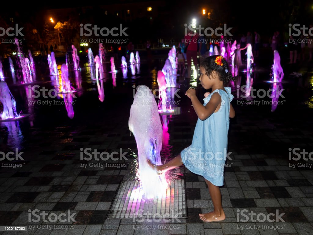 Mixed Jamaican Russian ethnicity little girl barefoot at night on a fountain with a color effect stock photo