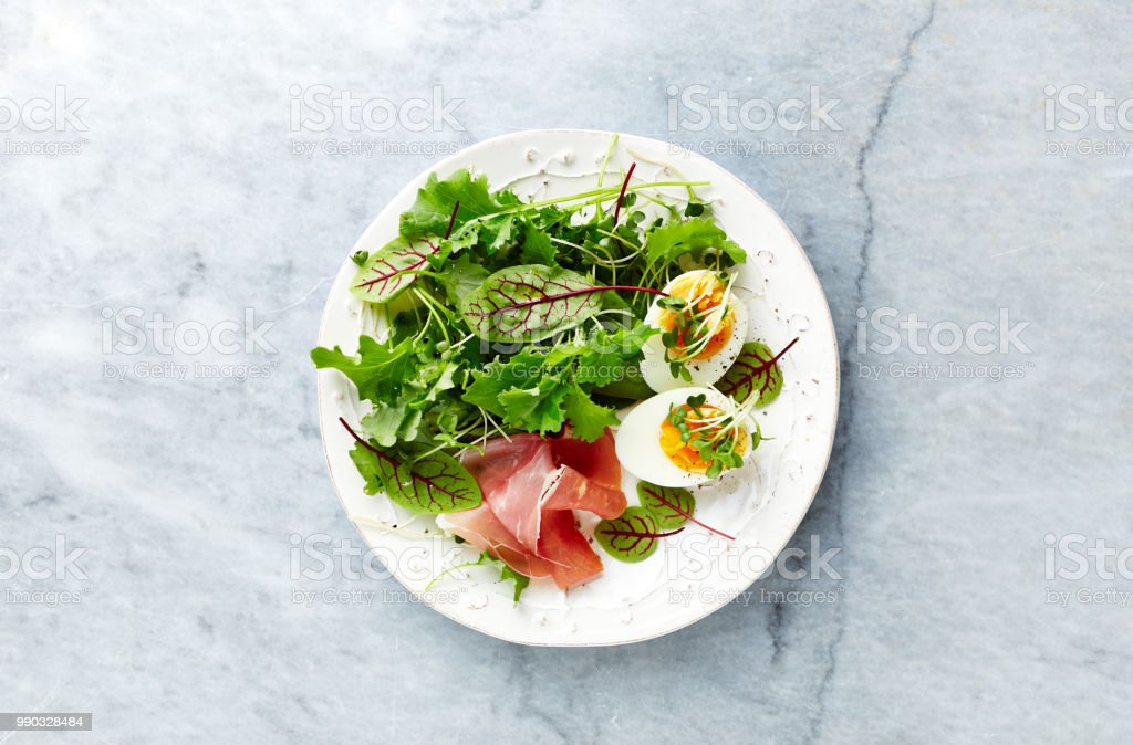 Mixed leaf salad with egg, serrano ham, and herbs. Healthy diet. Flat lay. Home made food stock photo