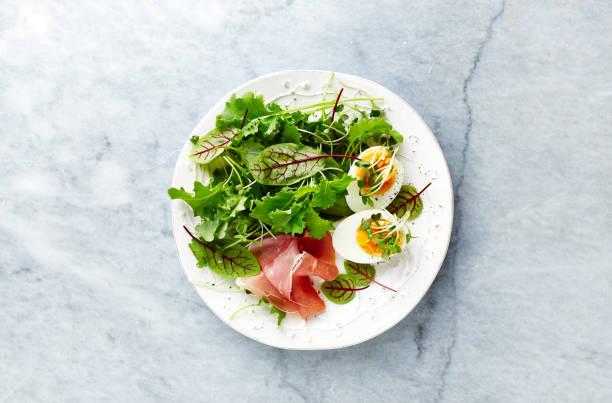 gemischter blattsalat mit ei, serrano-schinken und kräutern. gesunde ernährung. flach zu legen. hausgemachte speisen - radieschen salat stock-fotos und bilder