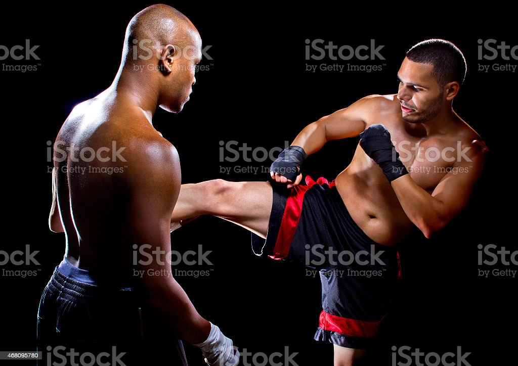 Mixed Martial Arts Instructor Teaching his Student How to Kick stock photo