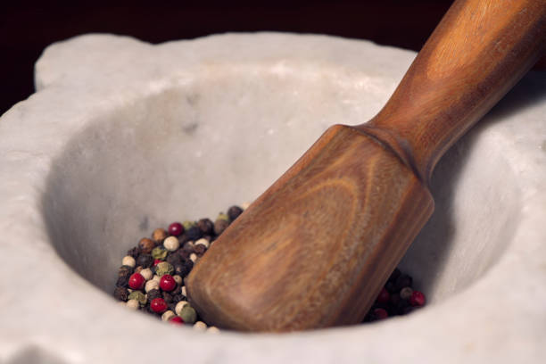 Mixed multi colored peppercorns in mortar and pestle. Close-up of Organic spices. stock photo
