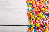 mixed multicolored candies on white wooden background. copy space, top view, flat lay.