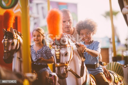 Multi-ethnic family boy having fun with father riding horse on merry-go-round amusement park ride