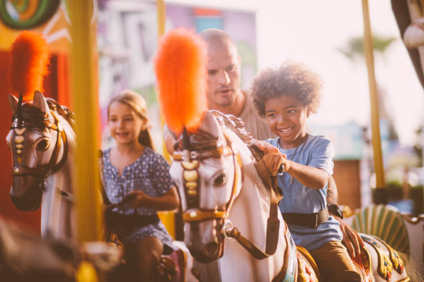 Mixed multi-ethnic family with father having fun on carousel ride stock photo