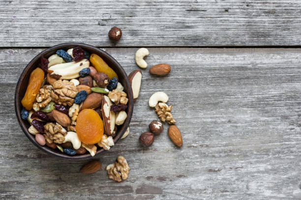 mixed nuts and dried fruits in a bowl - dried fruit stock photos and pictures