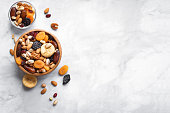Mixed nuts and dried fruits in wooden bowl on white marble background, copy space. Healthy snack - mix of organic nuts and dry fruits.