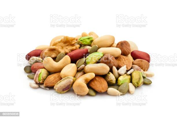 Macro shot of mixed nuts arranged in a heap isolated on white background. Nuts included in the composition are pistachios, hazelnut, pine nut, almonds, pumpkin seeds, macadamia nuts, sunflower seeds, peanuts, cashew and walnuts. DSRL studio photo taken with Canon EOS 5D Mk II and Canon EF 100mm f/2.8L Macro IS USM