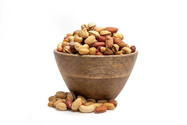mixed nuts in a wooden bowl isolated on white - frutos secos imagens e fotografias de stock