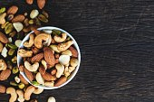 Healthy food and snack : mixed nuts in white ceramic bowl from above,  Walnut, pistachios, almonds, hazelnuts and cashews.'n'n