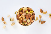 Healthy food and snack : mixed nuts in white ceramic bowl on white background from above, pistachios, almonds, hazelnuts and cashew