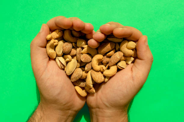 Mixed nuts in man's hands forming heart shape on green background. Top view. stock photo