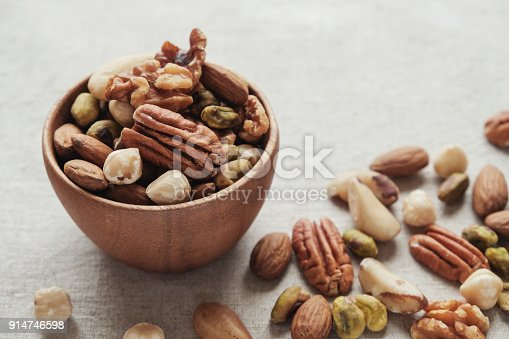 mixed nuts in wooden bowl, healthy fat and protein food and snack, ketogenic diet food