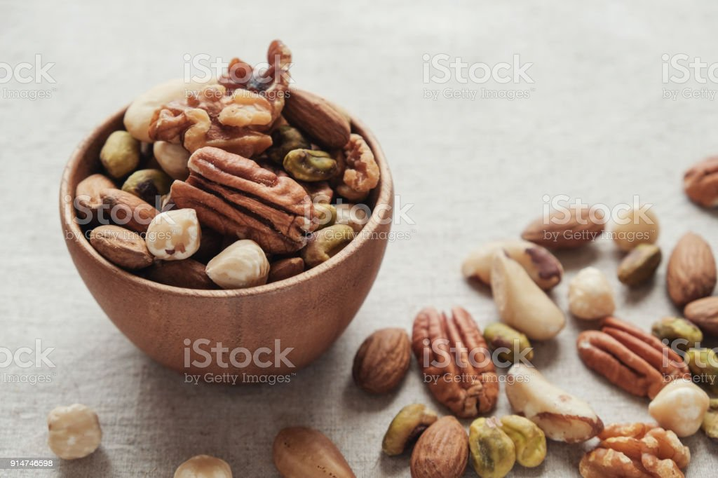 mixed nuts in wooden bowl, healthy fat and protein food and snack, ketogenic diet food stock photo