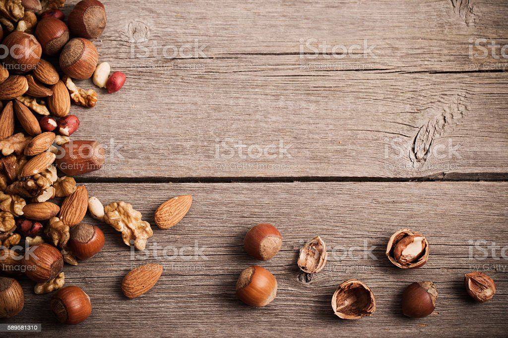 Mixed nuts on  old wooden background stock photo