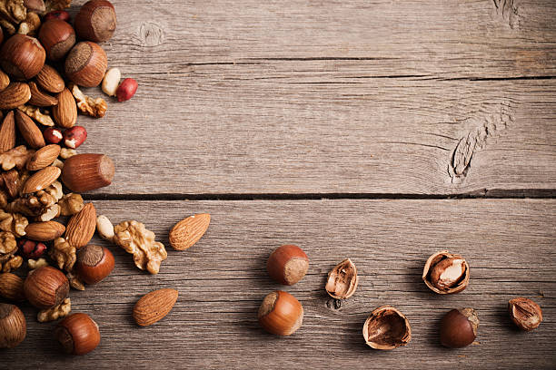 mixed nuts on  old wooden background - haselnuss baum stock-fotos und bilder