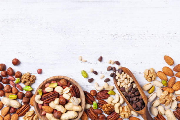 Mixed nuts on white wooden table top view. Healthy food and snack. Mixed nuts on white rustic wooden table top view. Healthy food and snack. method of preparation stock pictures, royalty-free photos & images