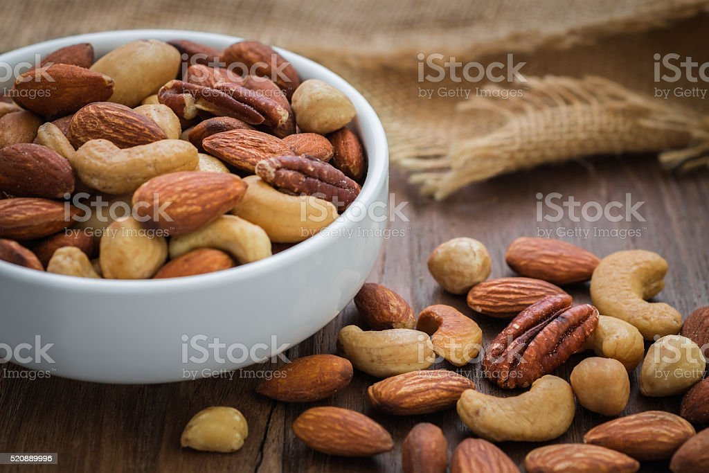 Mixed nuts on wooden table and bowl stock photo