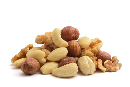 A pile of shelled hazelnuts, walnuts,cashew nuts and almonds, isolated on a white background.