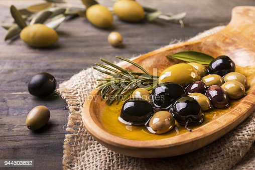 wooden bowl in the foreground with rosemary olives and virgin oil on the wooden table
