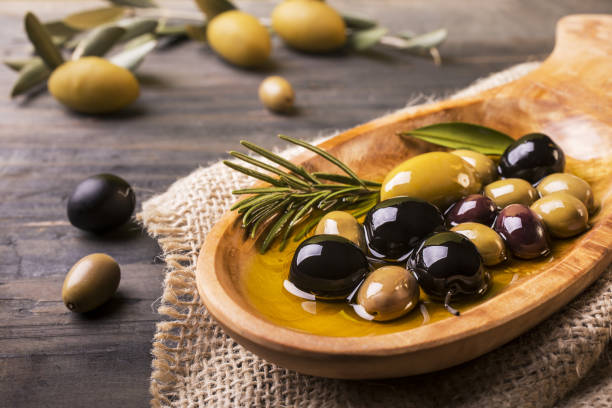 mixed olives with rosemary in the foreground wooden bowl in the foreground with rosemary olives and virgin oil on the wooden table olives stock pictures, royalty-free photos & images