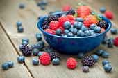 'A bowlful of delicious organic berries.  Strawberries, blackberries, blueberries and raspberries.  Shallow dof'