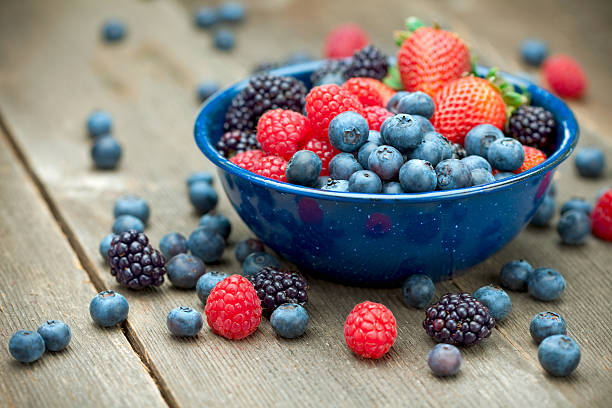 mixed organic berries - berry stock photos and pictures