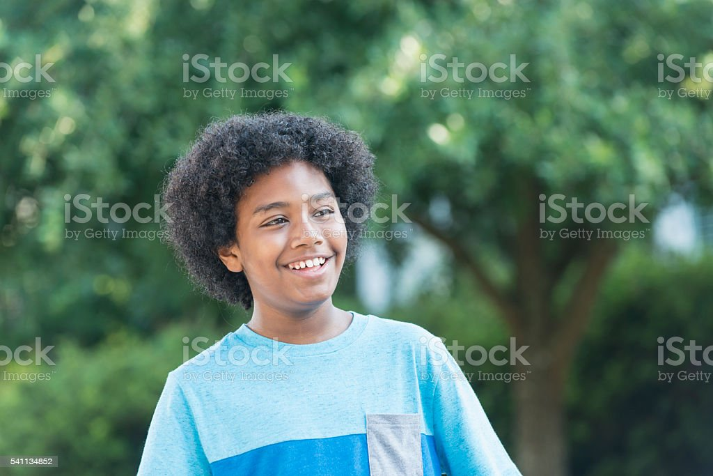 Mixed race 12 year old boy standing outdoors smiling stock photo