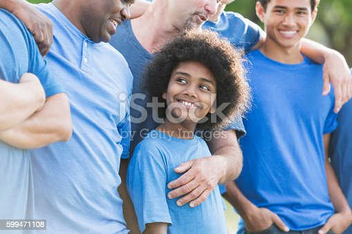1091098220 istock photo Mixed race African American boy with group of men 599471108