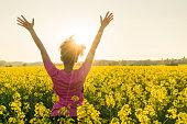 混血アフリカ系アメリカ人女の子若い女性アスリート ランナー ティーンエイ ジャー黄金の夕日や日の出の腕上げた黄色い花のフィールドで祝う