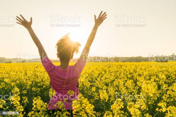 Photo of Mixed race African American girl female young woman athlete runner teenager in golden sunset or sunrise arms raised celebrating in field of yellow flowers