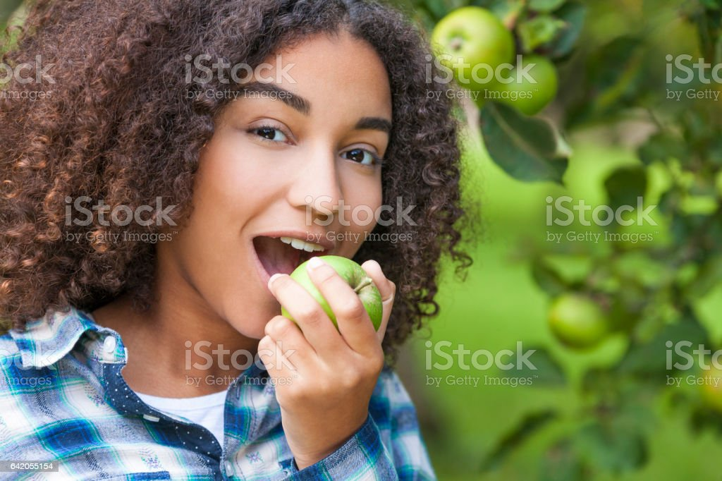 Mixed race African American girl teenager female child eating an organic green apple stock photo