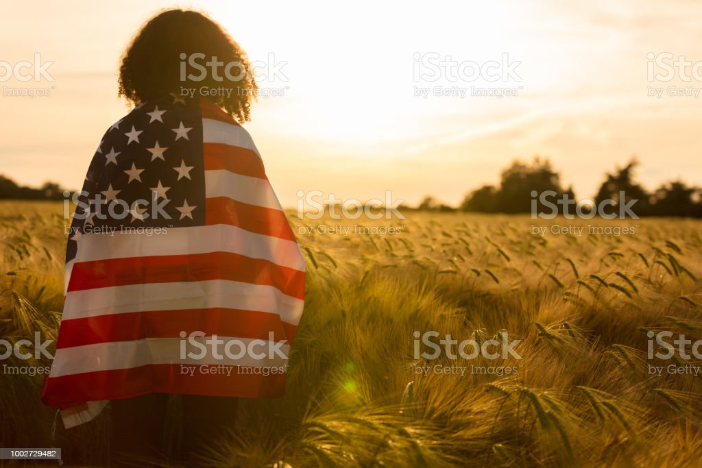Mixed race African American girl teenager female young woman in a field of wheat or barley crops wrapped in USA stars and stripes flag in golden sunset evening sunshine stock photo